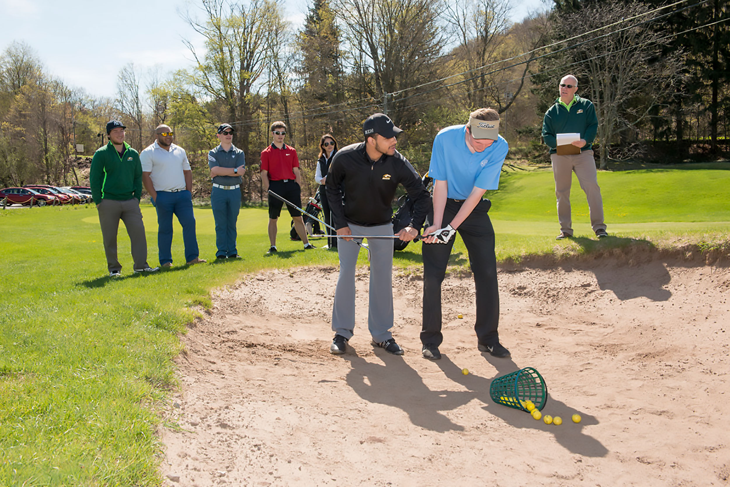 Golfing students and professors standing in sand pit