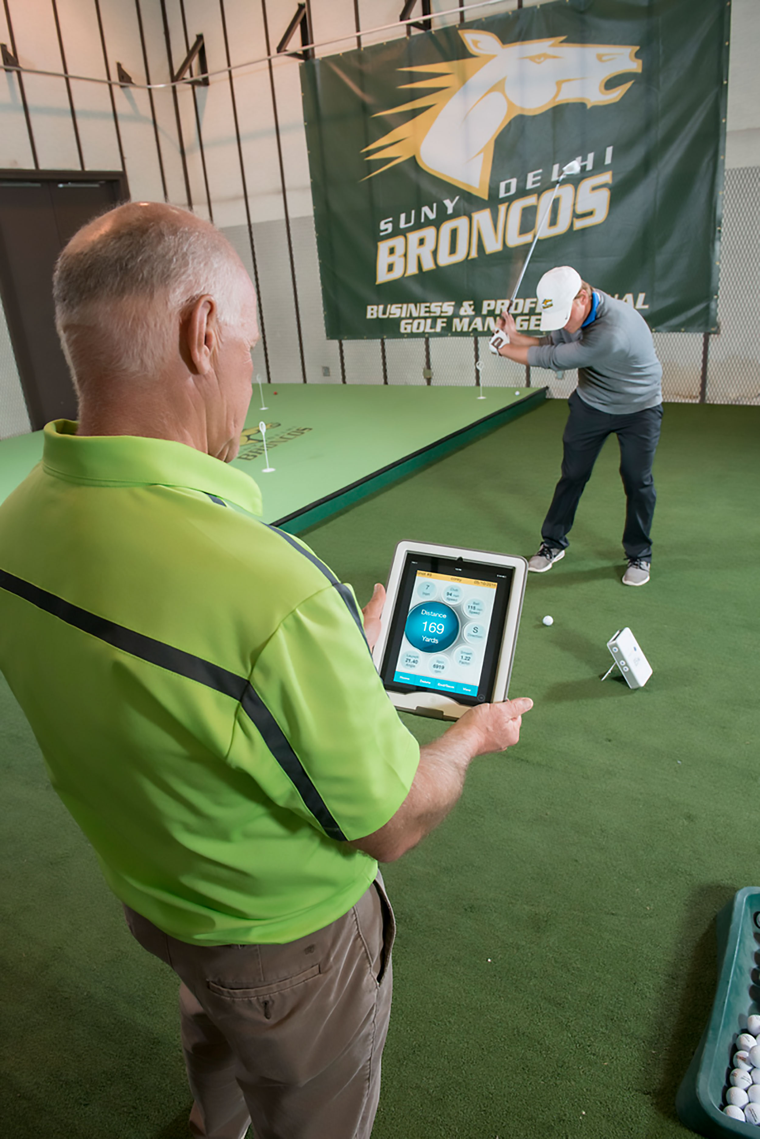 Student in golfing indoors with professor looking at tablet