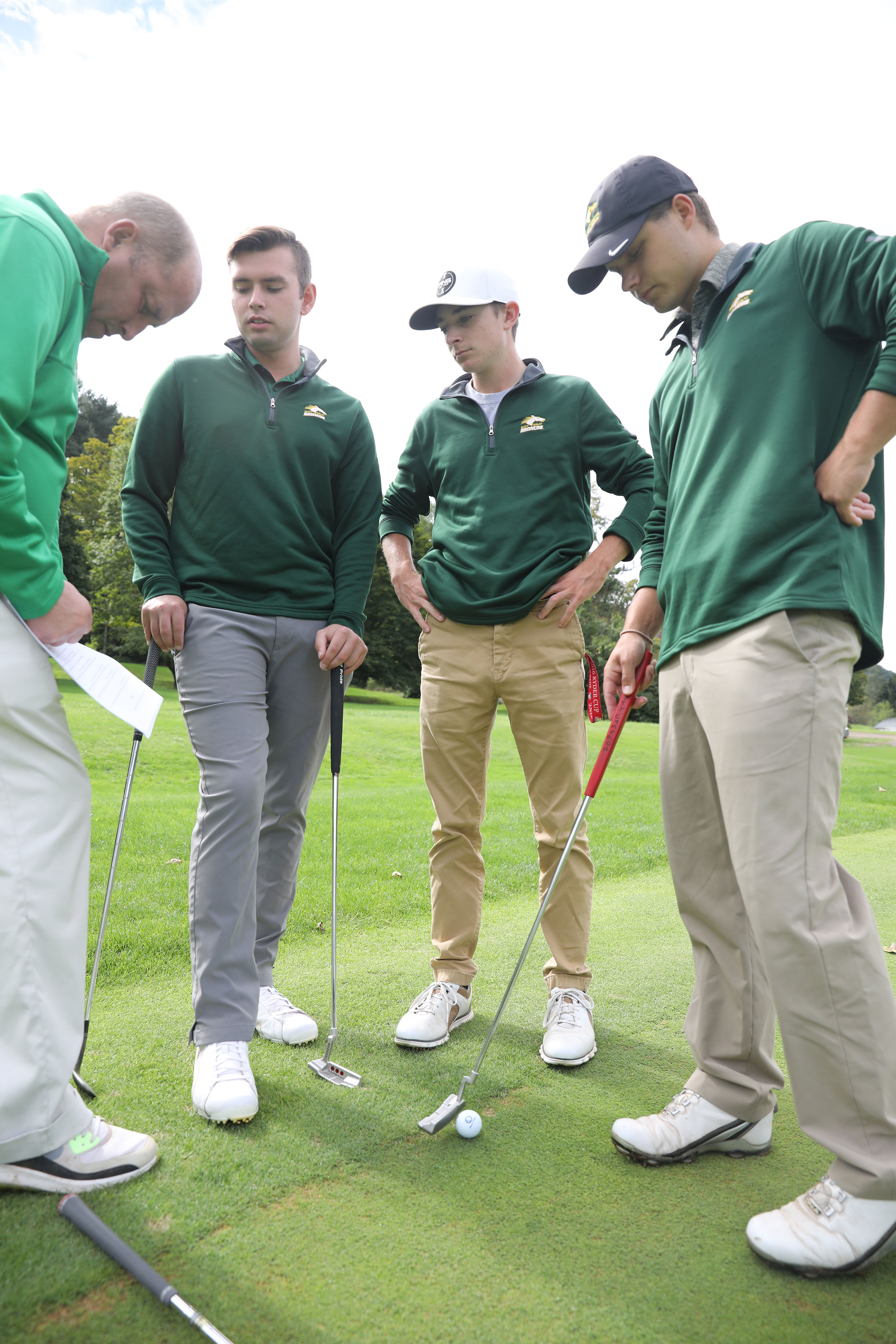 Four golfers looking down at a gof ball