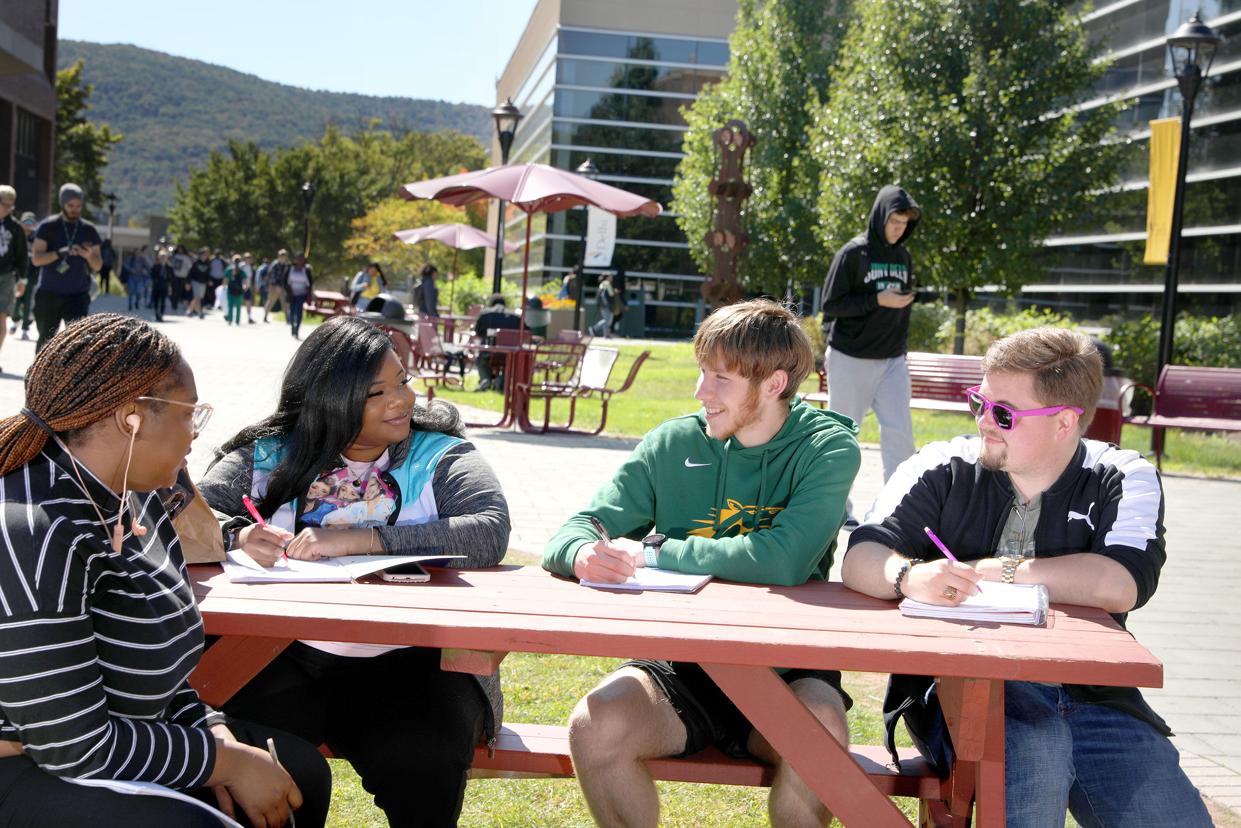 Students sitting at picnic table on campus