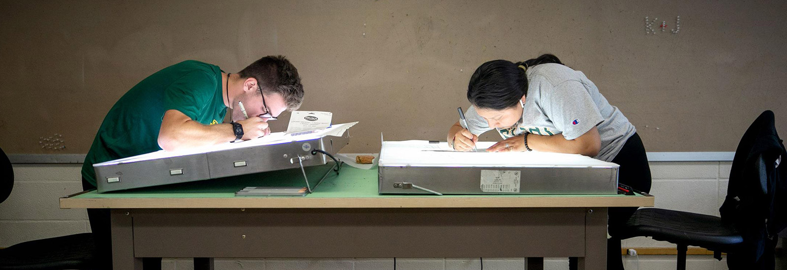 Architectural students drawing on a light table