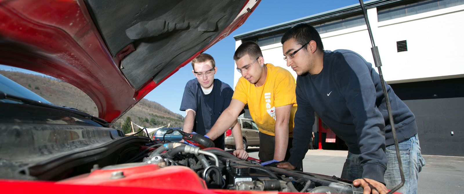 Three students working on a car engine