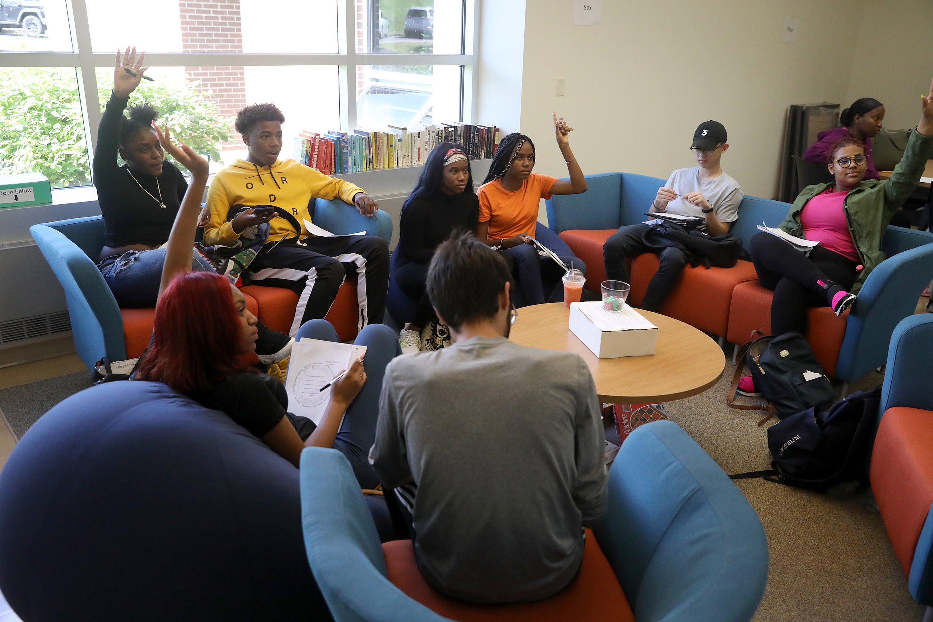 Students sitting in chairs around the room having a discussion