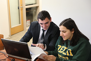Student helps another student with their taxes on their laptop