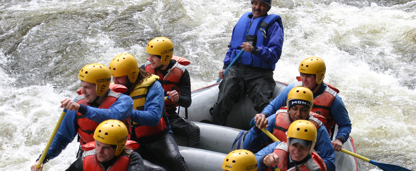Students whitewater rafting in a rapid on the river