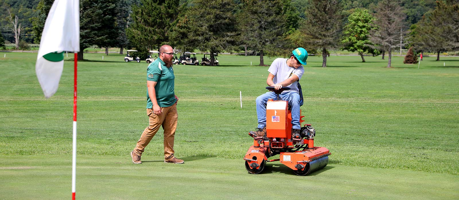 Professor teaching a student how to groom a golf green