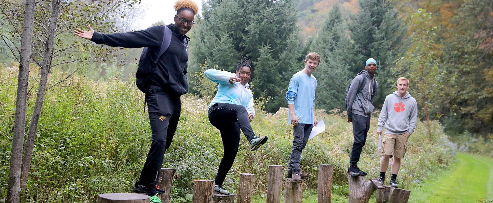 Students balancing on obstacle course tree stumps