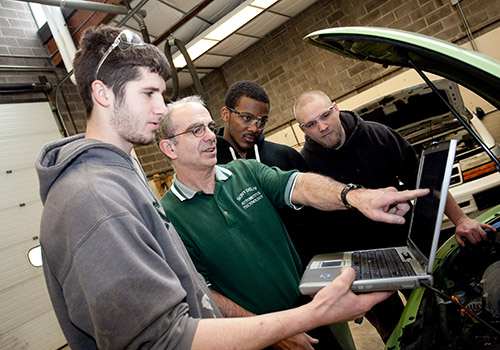 Students and instructor working on a laptop connected to a car