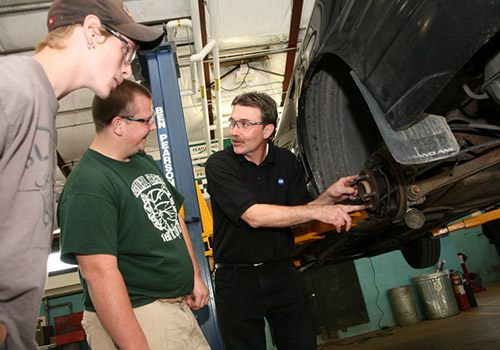 Students working on a car with an instructor