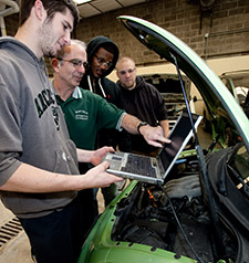 Instructor Shows Automotive Technology Students How to Use Computer Diagnostics for Automotive Repair