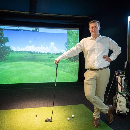 Student in front of golfing screen