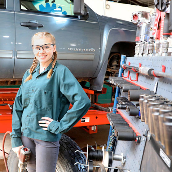 Female automotive student in front of a truck on a lift