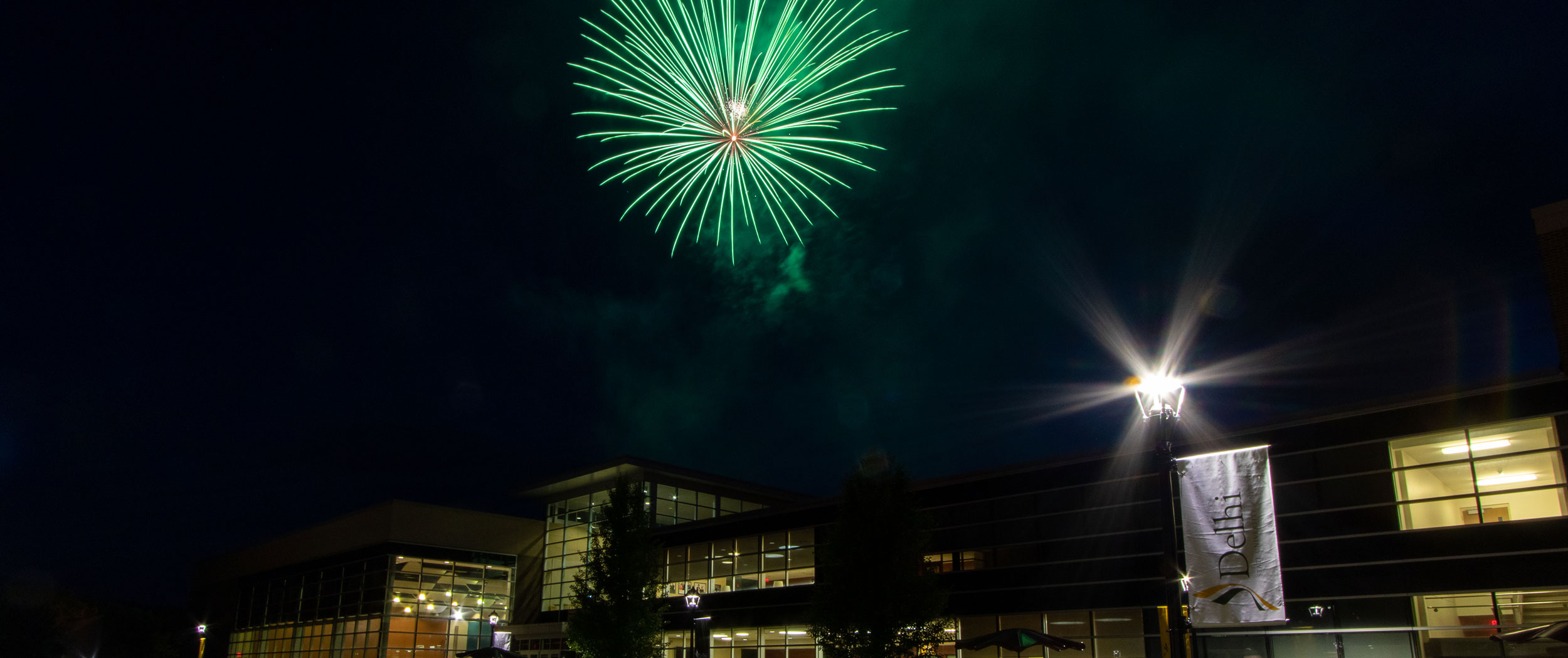 SUNY Delhi at night with fireworks in the sky