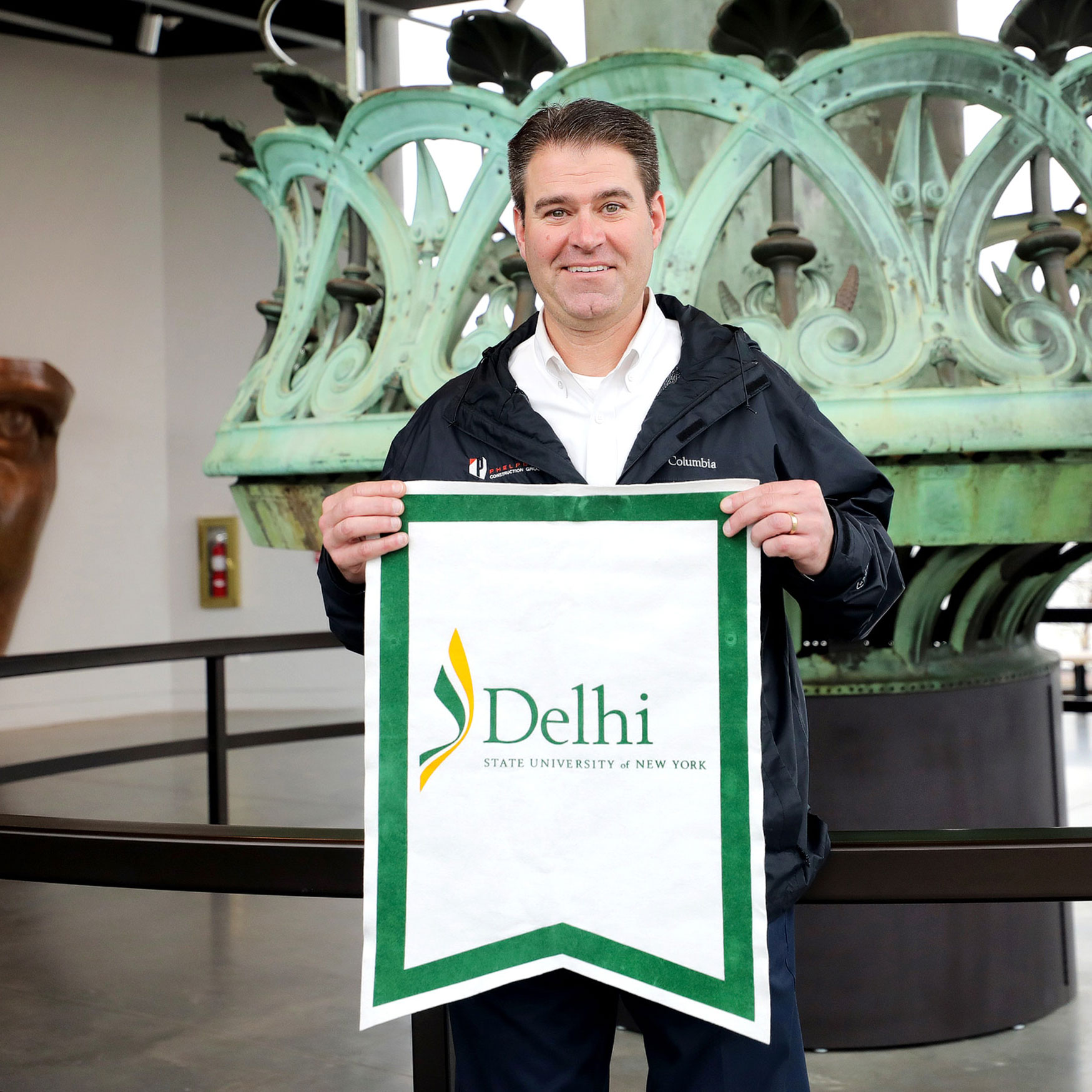 Jeff Rainforth holding up SUNY Delhi banner